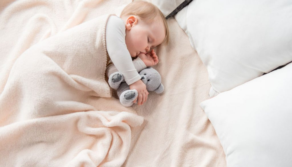 Tranquil infant dreaming with lovely toy
